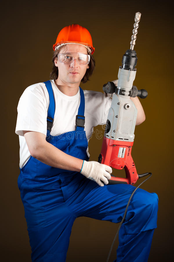 Worker with a machine drill. Worker holding a machine drill royalty free stock image