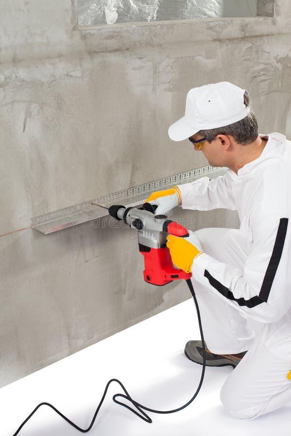 Worker making a hole trough a lath. Construction worker making a hole trough a lath stock photo