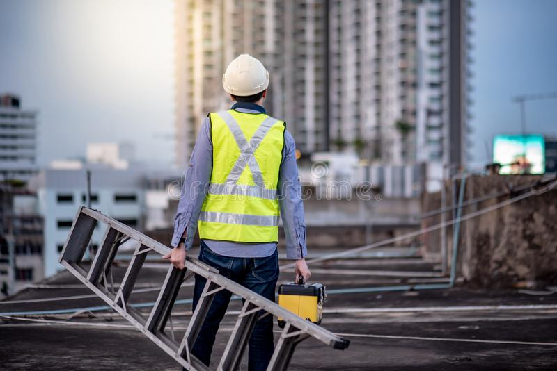 Worker man carrying aluminium ladder and tool box stock photography