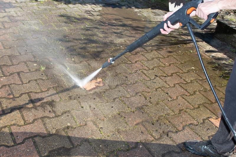 Worker man cleaning with high pressure water jet. A worker man cleaning with high pressure water jet stock photography