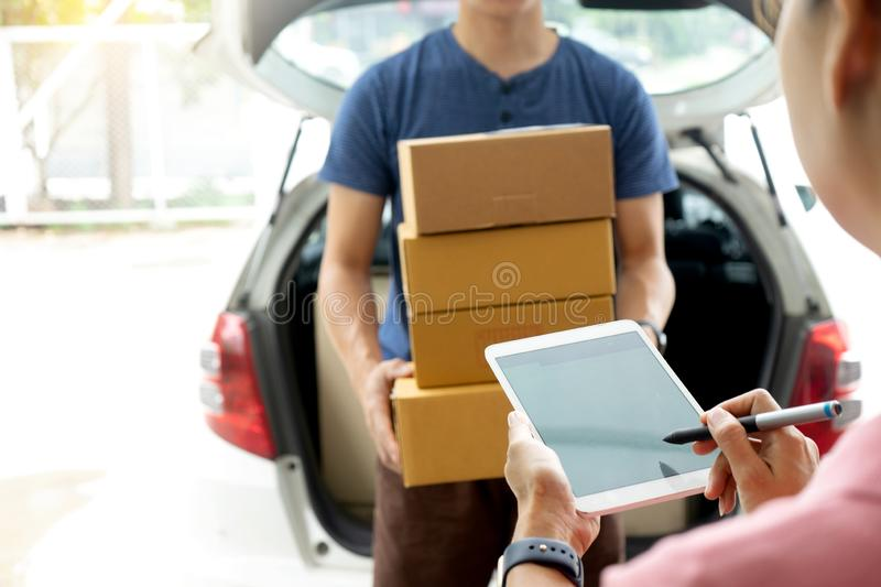 Worker man delivery the boxs to woman. Home or office , with tablet for sign stock photography