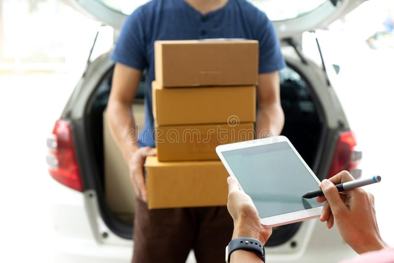 Worker man delivery the boxs to woman. Home or office , with tablet for sign royalty free stock images