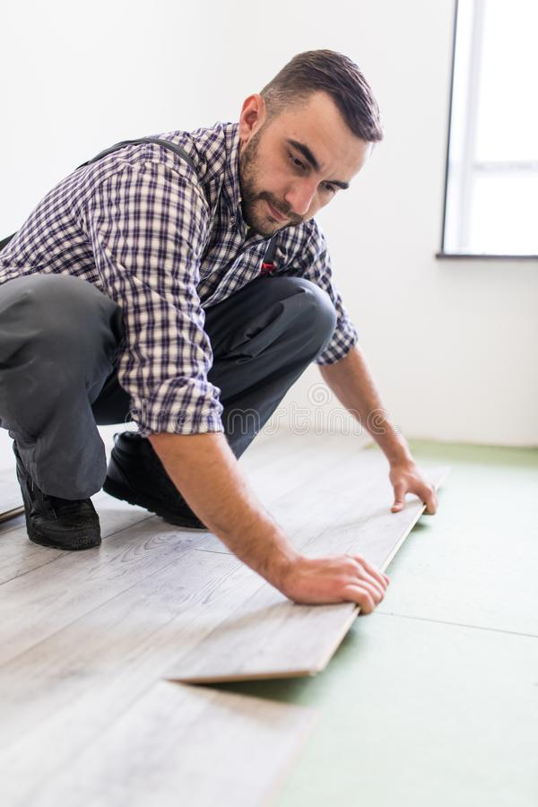 Worker Man laying laminate flooring at home room. Man work laying laminate flooring at home royalty free stock photo