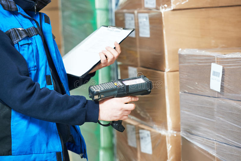 Worker man scanning package in warehouse. Male worker scanning package with barcode scanner in modern warehouse stock images