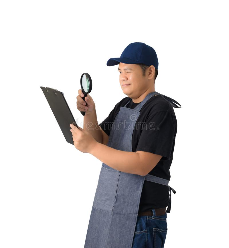 worker man or Serviceman in Black shirt and apron is holding clipboard and use Magnifying glass isolated stock image