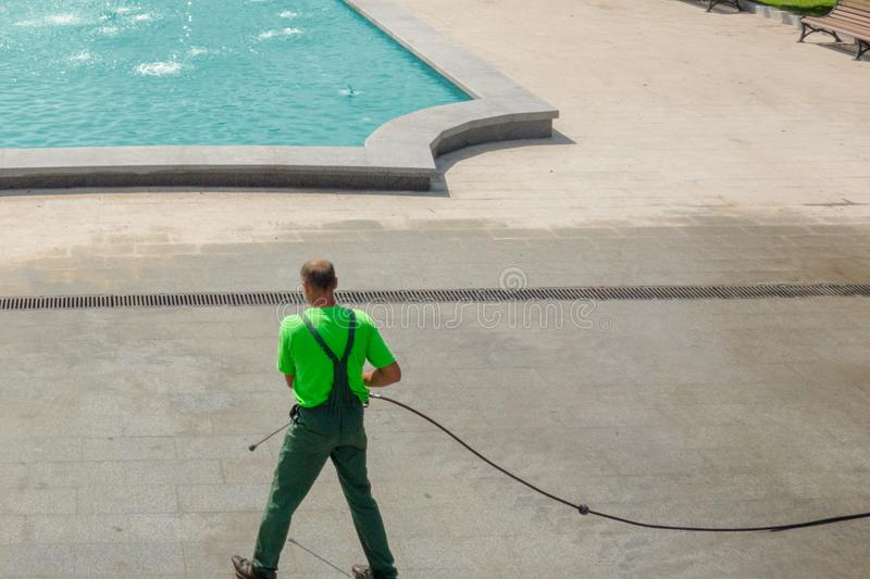 Worker man in uniform washes street or park sidewalk near water pool or fountain. Municipal service of city cleaning process. Guy stock image