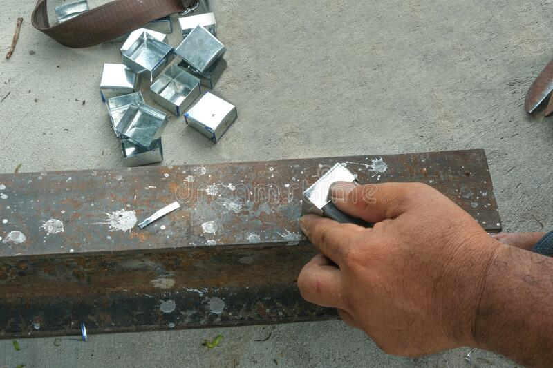 Worker man use hand make dice aluminium square box. capenter work with strong iron on concrete floor. part of zinc material prepar. E for building roof in house stock photo