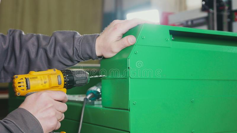 Worker man using an electric hand drill - making hole in green metal machine royalty free stock photo