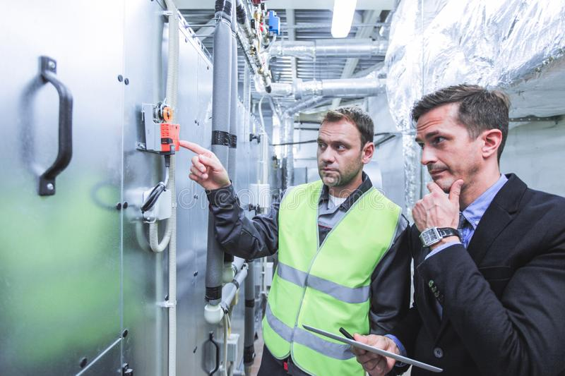 Worker and manager in switchgear room stock image