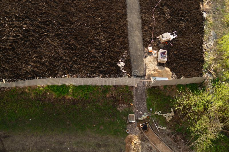 Worker manually paves a way to future parking lot. builder is busy with construction work. aerial view. manual labor concept royalty free stock image