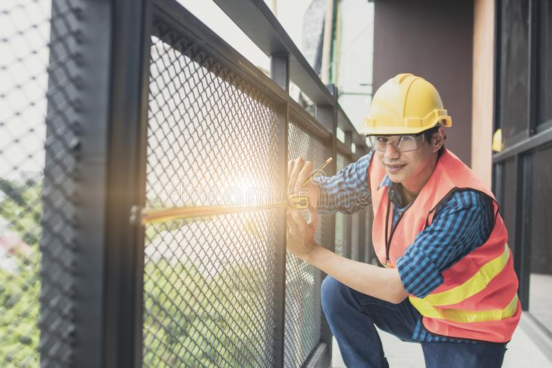 Worker measure iron balcony by Measuring Tape in construction si stock photos