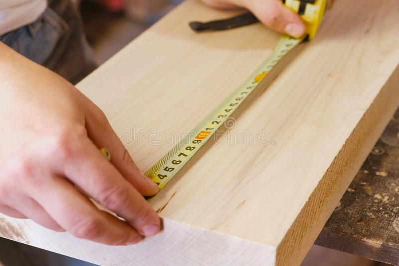 Worker measures the tape measure and pencil distance on the wood Board. Joinery. Hands close-up. stock photo