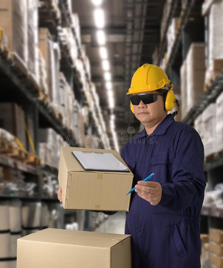 Worker in Mechanic Jumpsuit Delivering products Sign the signature on the product receipt form with parcel boxes. Blurred the background of the warehouse royalty free stock images