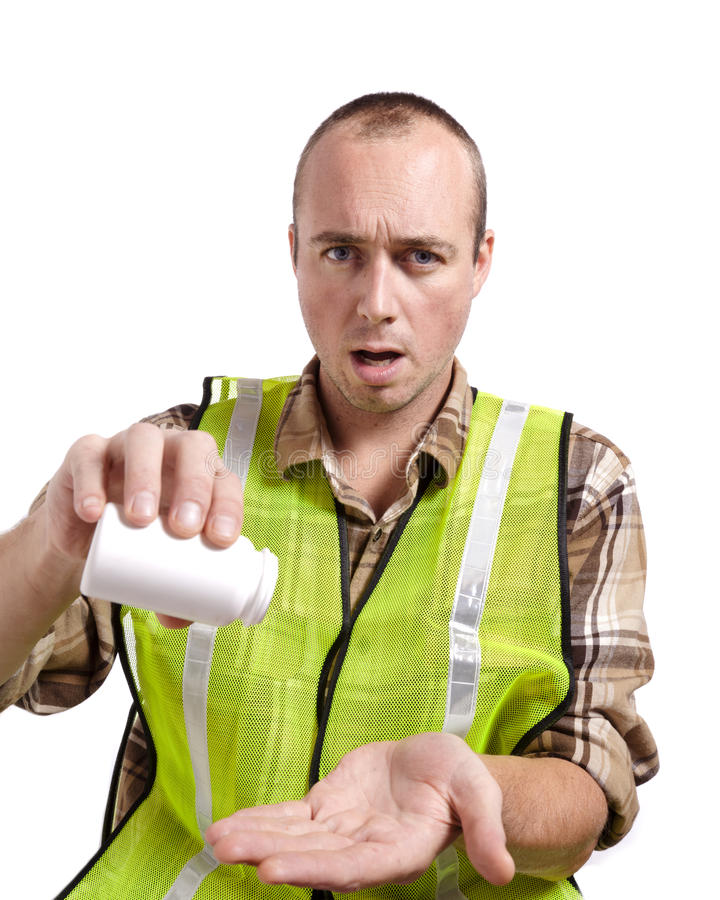 Worker and Medication. A young man in construction safety vest has run out of medicine stock photos