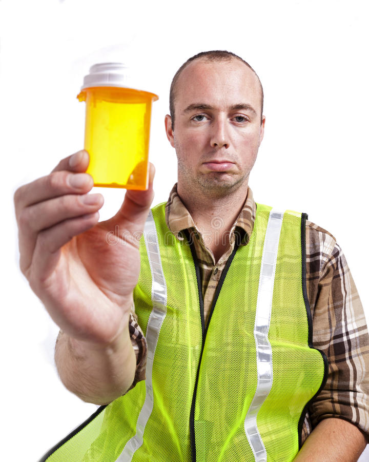 Worker and Medication. A young man in construction safety vest has run out of medicine royalty free stock photography