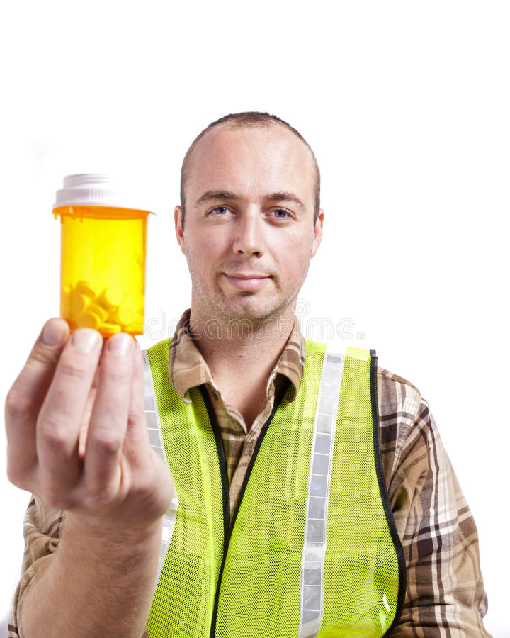 Worker and Medication. A young man in construction safety vest has run out of medicine stock photography