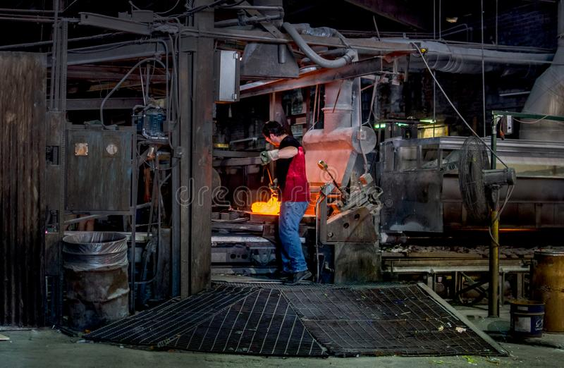 A worker mixes molten glass into a machine at glass factory. Sept 27 2019 Kokomo Indiana USA; A worker mixes melted glass into designs before feeding it into a stock image