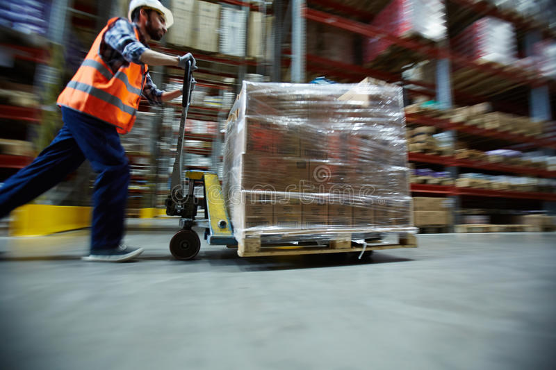 Worker Moving Retail Merchandise in Large warehouse royalty free stock image