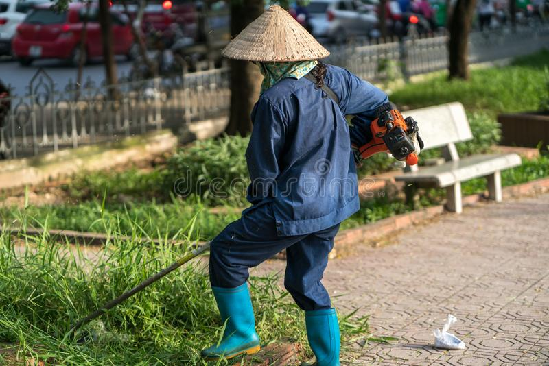Worker mowing lawn with grass trimmer outdoors in Hanoi city, Vietnam stock image