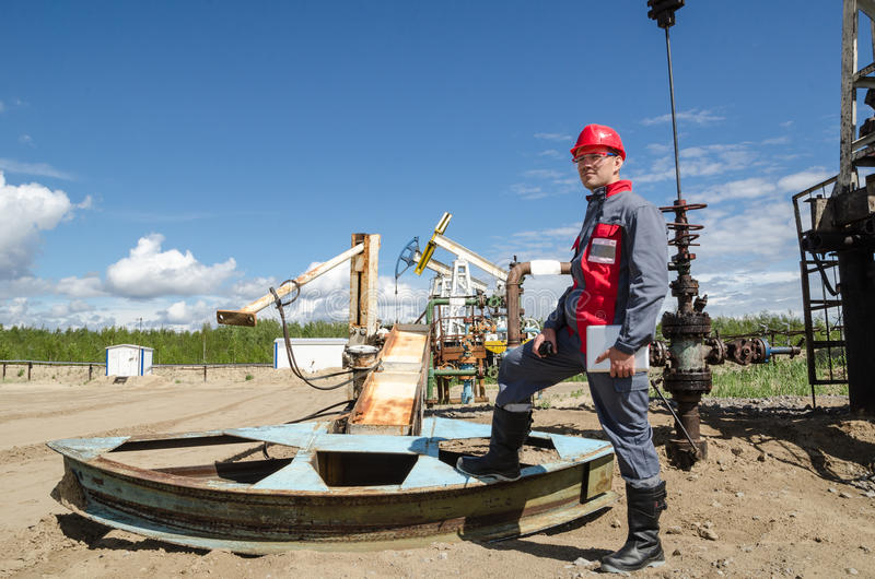 Worker near broken pump jack. Holding radio and tablet computer in the oilfield. Pump jacks and wellhead background. Oil and gas concept royalty free stock image