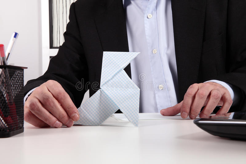 Worker in office. Worker wasting time with origami stock photography