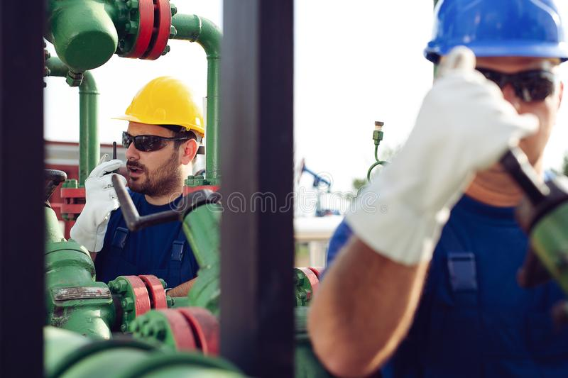 Worker on oil pump looks at laptop and speaking in a radio station. Young Worker on oil pump looks at laptop and speaking in a radio station royalty free stock photos