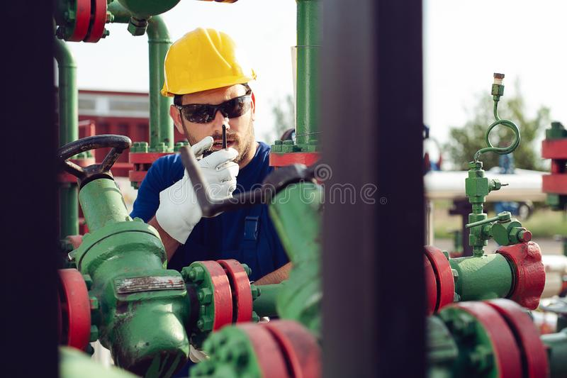 Worker on oil pump looks at laptop and speaking in a radio station. Young Worker on oil pump looks at laptop and speaking in a radio station royalty free stock photography