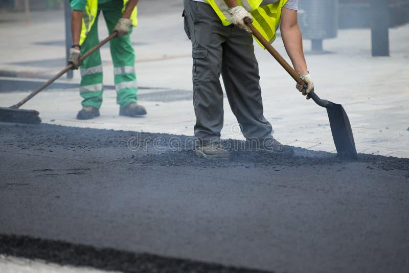 Worker operating asphalt paver machine stock images