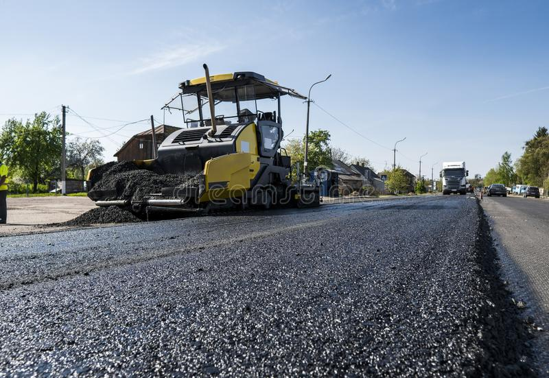 Worker operating asphalt paver machine during road construction and repairing works. A paver finisher, asphalt finisher. Or paving machine placing a layer of royalty free stock images