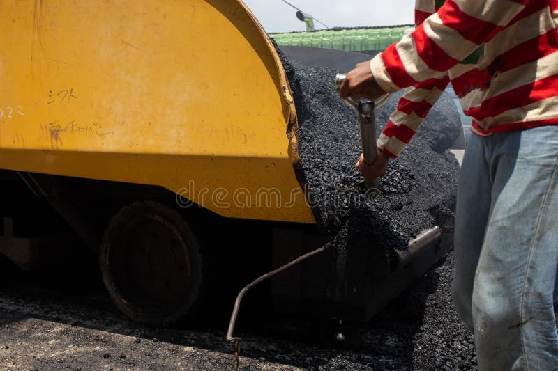 Worker operating asphalt road city,Construction work for a road and highway repair,Concept: Transportation symbol for vehicle. Worker operating asphalt road city stock photos