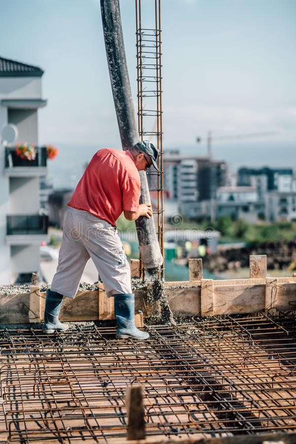 Industrial worker operating cement pump, industrial machinery details and construction site royalty free stock photo