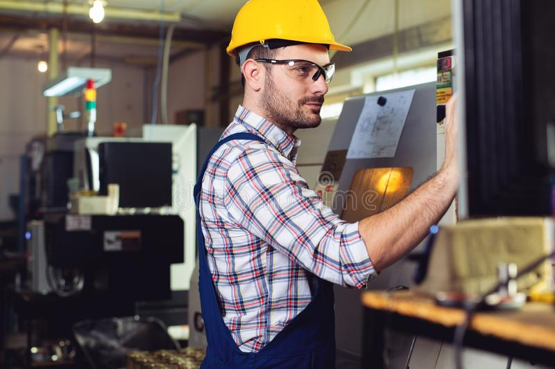 Worker operating CNC machine center royalty free stock photography