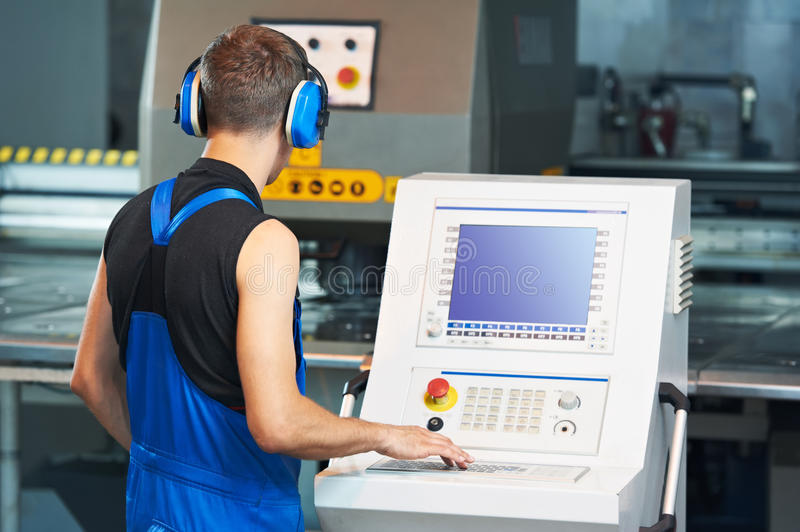 Worker operating cnc punch press royalty free stock photos