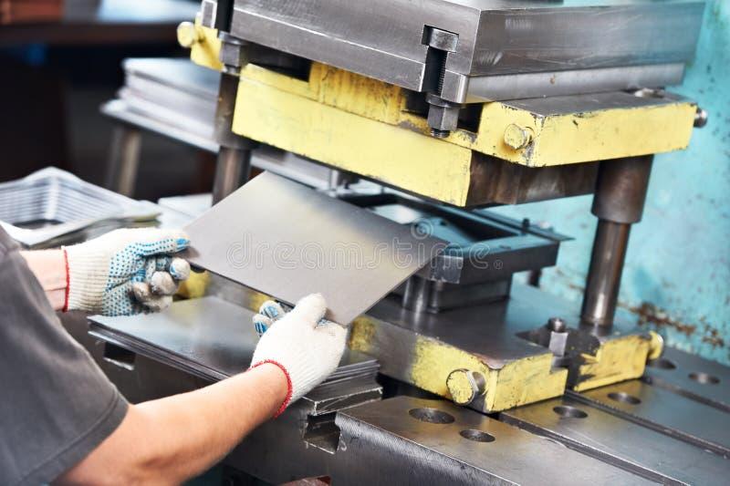 Worker operating metal sheet press machine stock image