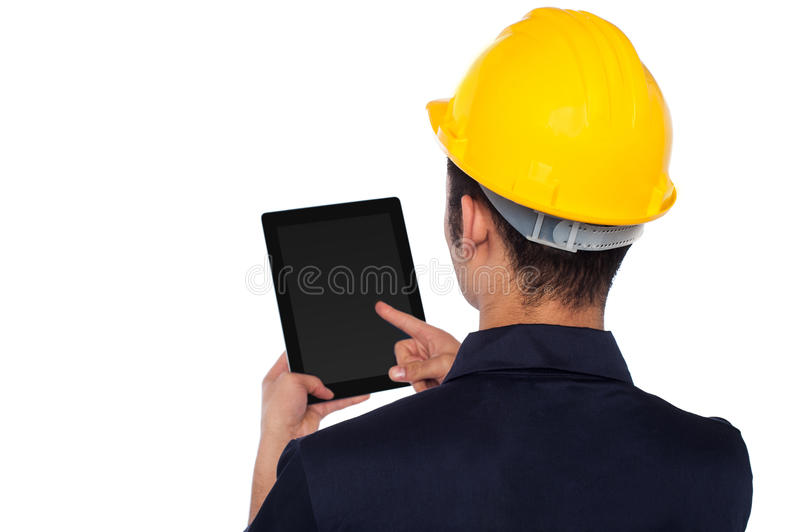 Worker operating tablet device, back pose. Young construction worker operating touch pad device stock images