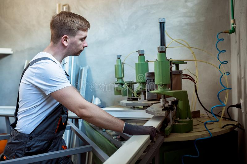 Worker operating welding machine in factory. royalty free stock photo
