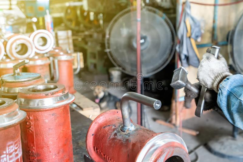 Worker or operator cleaning welding seam remove by knock with hammer and chisel at factory royalty free stock images