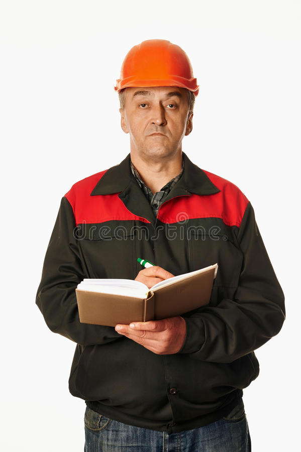 Worker in a orange hardhat writes in a notebook stock image