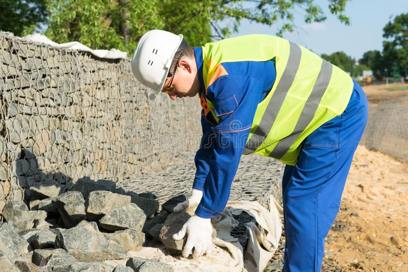 A worker in overalls at a construction site raises a stone from the ground stock photos