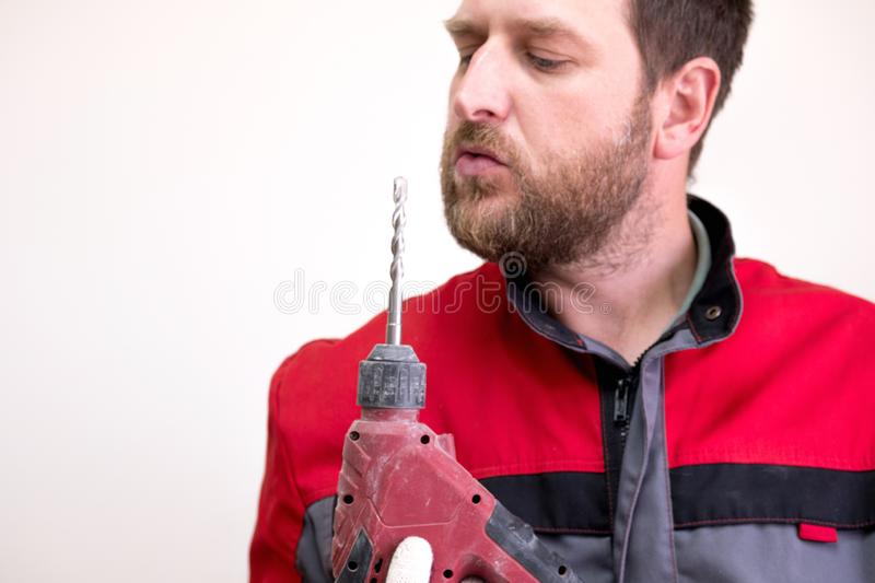 A worker in overalls holds a drill to his face and blows on the drill to cool stock images