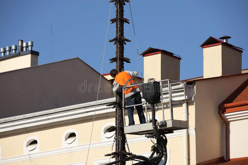 The worker in overalls works at height in a building mechanical lifting basket. Repair and construction work on the renovation of stock photography