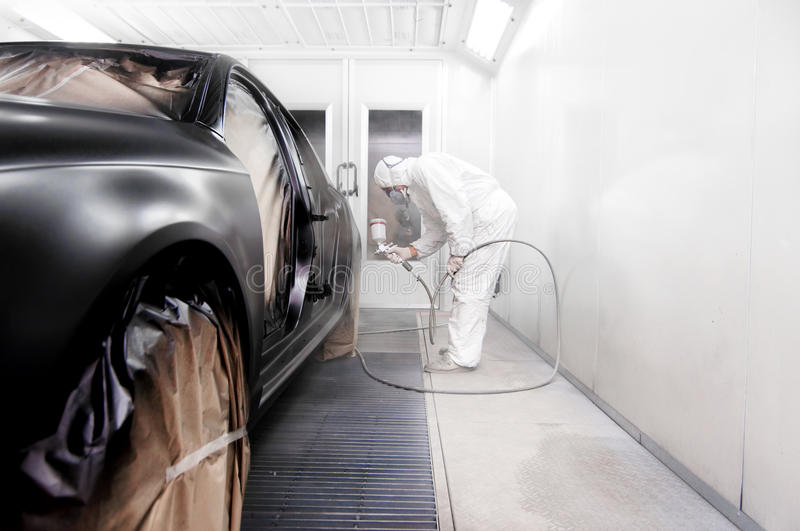Worker painting a black car in a special garage stock image