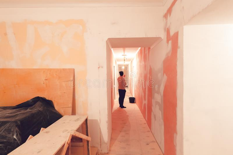 Worker is painting the ceiling by paint roller in corridor an apartment is inder construction, remodeling, renovation royalty free stock photography