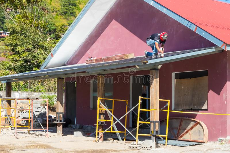 Worker painting the roof of a building under renovation in a sunny day stock images