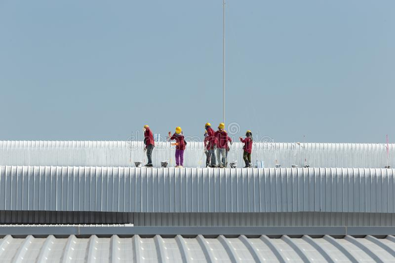 Worker painting on the roof of factory royalty free stock images