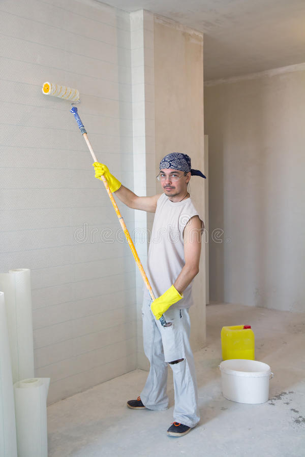 Worker painting wallpaper. House improvement. Young man painting wallpaper with painting roller royalty free stock photography
