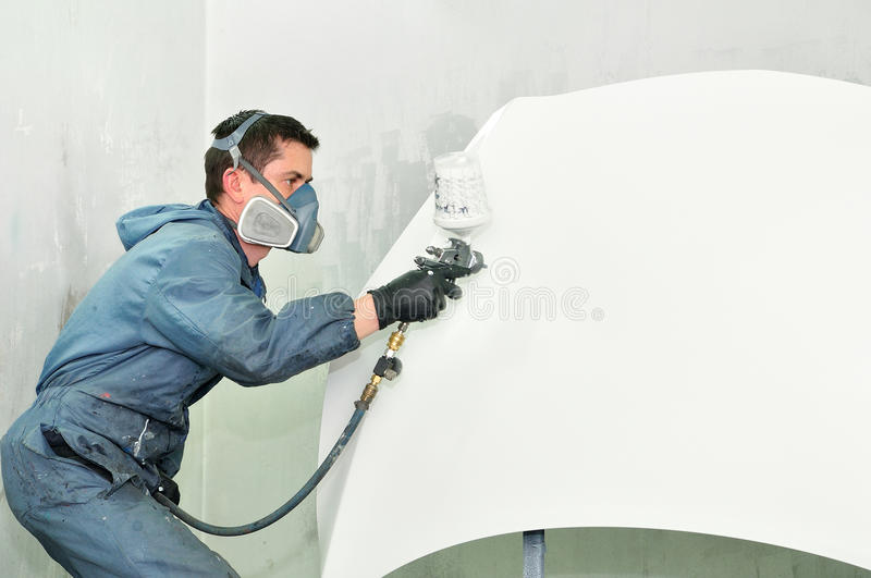 Worker painting white car bonnet. Professional body shop worker painting white car bonnet royalty free stock photo