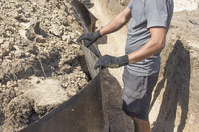 Worker perform waterproofing the foundation for building a house. Worker installing resin foil under the foundation of the house. Waterproof system stock images