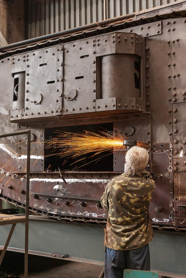 The worker performs grinding work on the sidepiece of the English heavy tank of the First World War. The worker performs grinding work on the sidepiece of the royalty free stock photo