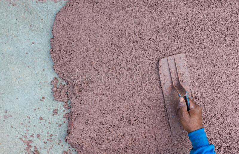 Worker plastering cement at wall or floor for building house. Construction worker plastering and smoothing concrete wall with ceme royalty free stock photos